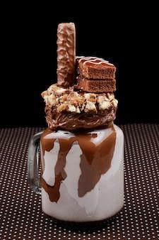브라우니 케이크, 초콜릿 페이스트 및 과자를 곁들인 초콜렛 익스트림 밀크 쉐이크. 미친 freakshake 음식 트렌드. 공간 복사