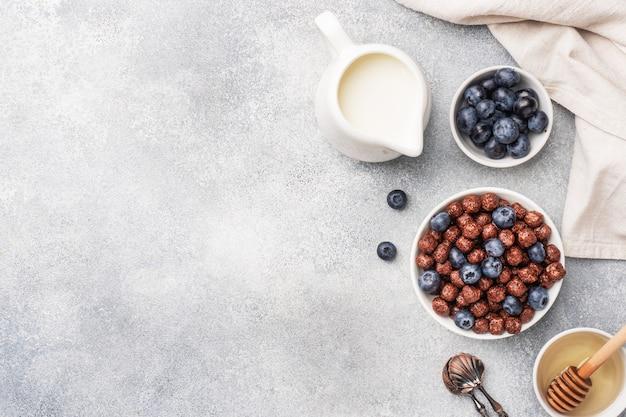 신선한 블루 베리, 꿀, 우유와 함께 천연 시리얼로 만든 초콜릿 플레이크