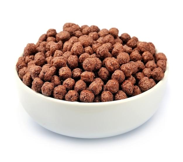 Шоколадные хлопья на белой тарелке изолированы крупным планом. шоколадные шарики. завтрак.