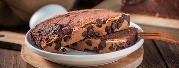 초콜릿 맛 재료와 나무 트레이 배경 테이블에 대만 전통 스폰지 케이크 (대만 카스텔라 kasutera)를 닫습니다.