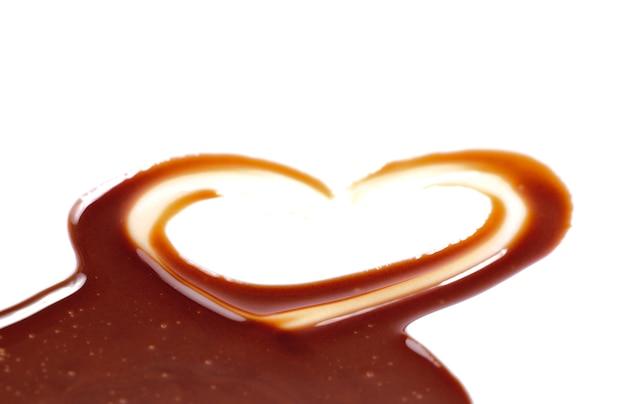 Поток шоколада, изолированные на белом фоне крупным планом, в форме сердца