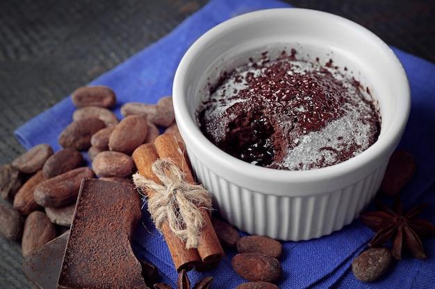 Шоколадный торт с помадкой в чашке на деревянном столе крупным планом