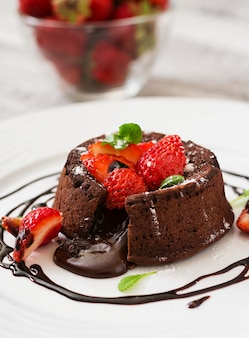 Chocolate fondant (cupcake) with strawberries and powdered sugar
