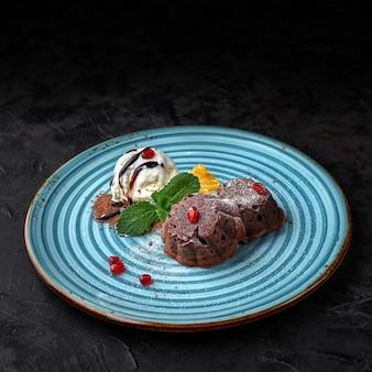Шоколадный фондан на синей тарелке с мороженым и ягодами на темном столе