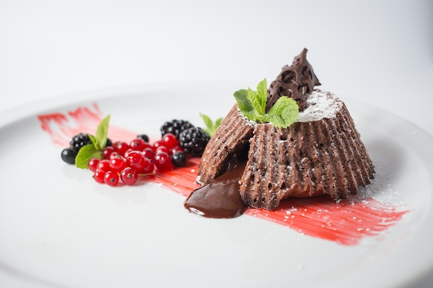 Шоколадный фондан с ягодами и мятой на белой тарелке.