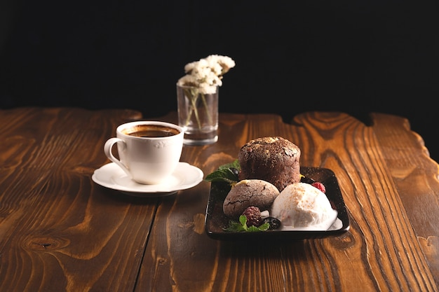 Chocolate fondant with ice cream and berries on a wooden restaurant table next to a cup of coffee