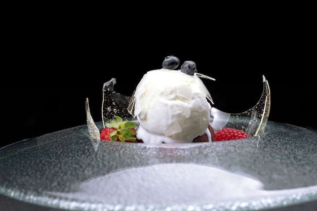 Chocolate fondant with ice cream, on a transparent plate, on a black background