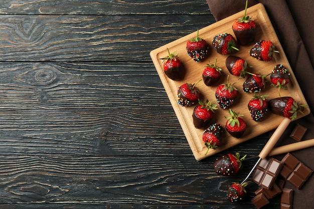 초콜릿 퐁듀. 나무 배경, 평면도에 초콜릿 딸기
