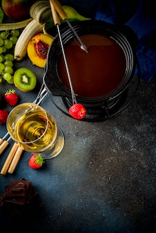 Chocolate fondue in traditional fondue pot, with forks,  white wine, assorted various berries and fruit, copy space