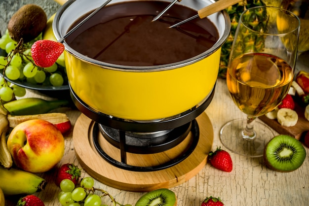 Chocolate fondue in traditional fondue pot, with forks,  white wine, assorted various berries and fruit