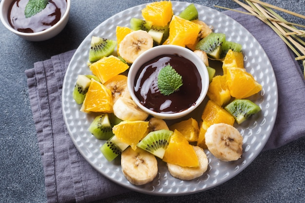 Chocolate fondue with fruit on a dark concrete background. concept summer party. copy space