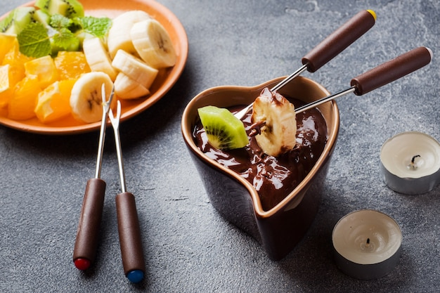 Chocolate fondue with fruit on a dark concrete .  summer party.