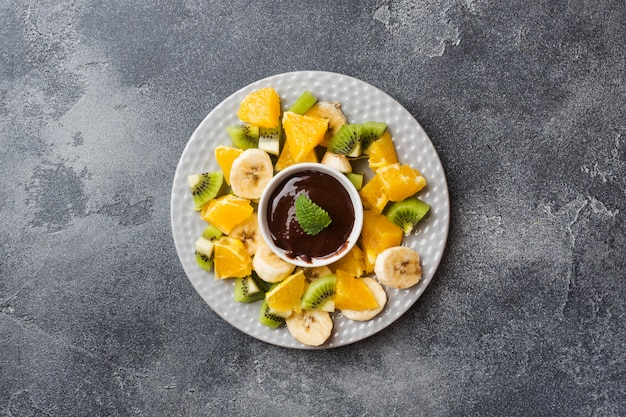 Chocolate fondue with fruit on a dark concrete
