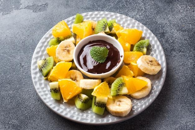 暗いコンクリートのテーブルにフルーツとチョコレートのフォンデュ。コンセプトの夏のパーティー。コピースペース