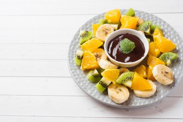 白いテーブルにフルーツとチョコレートのフォンデュ。コンセプトの夏のパーティー。コピースペース