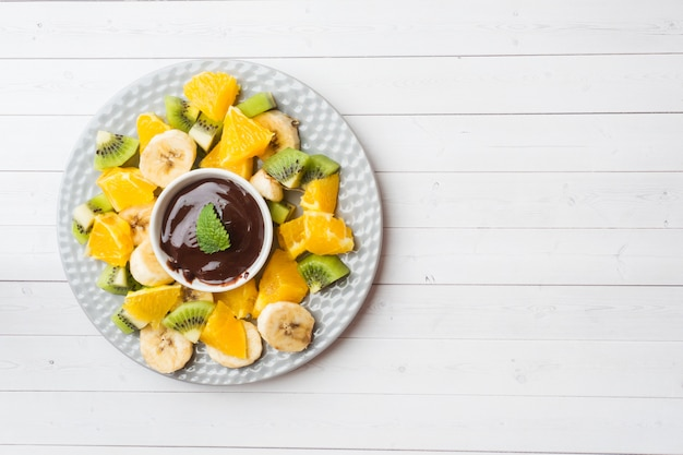 Chocolate fondue with fruit on white table