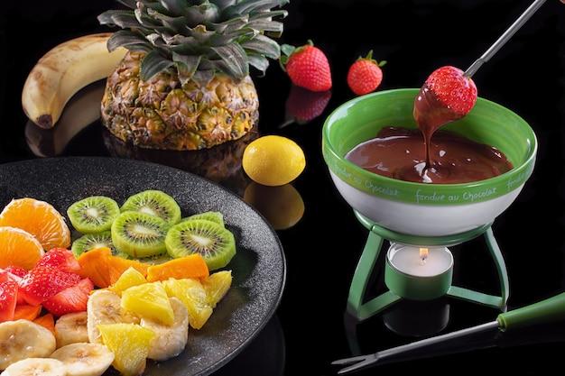 Chocolate fondue with fruits assortment on black mirror background.