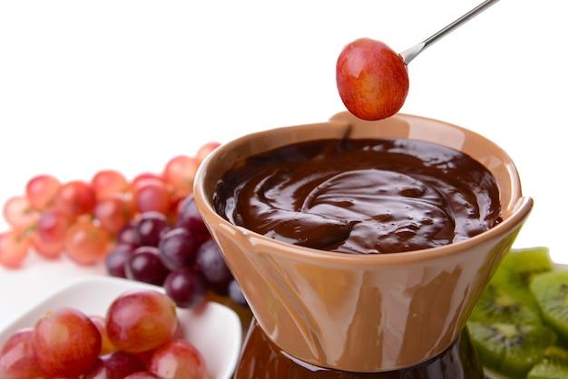 スライスしたフルーツとチョコレートフォンデュ、白で隔離