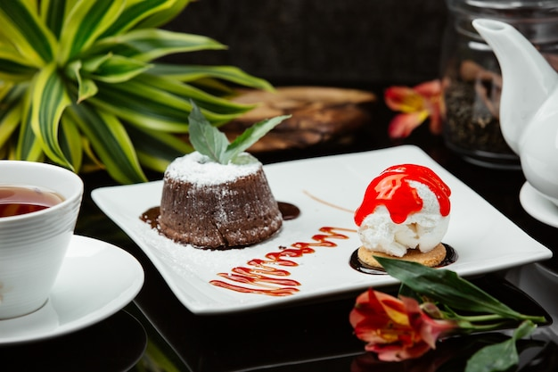 Chocolate fondue with whipping cream, mint and an icecream ball with red sauce.