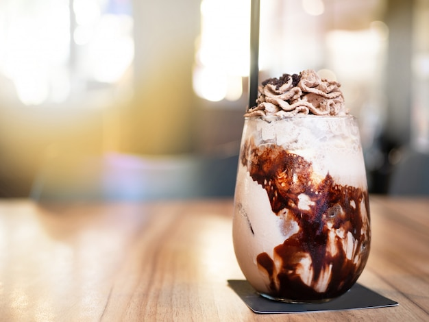 Chocolate frappe with whip cream above. put on the wooden table.
