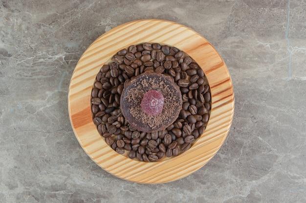 木の板にチョコレートのつや消しケーキとコーヒー豆