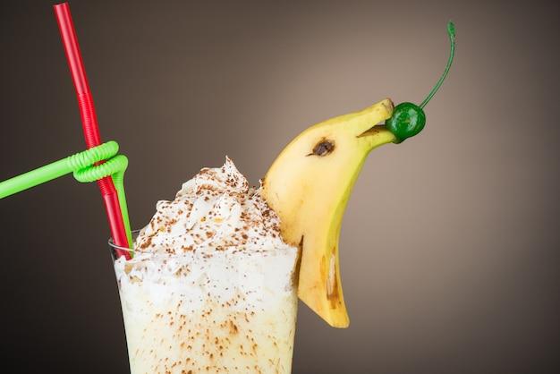 Шоколадно-фруктовый коктейль-мороженое с бананом на коричневом фоне летний тропический смузи