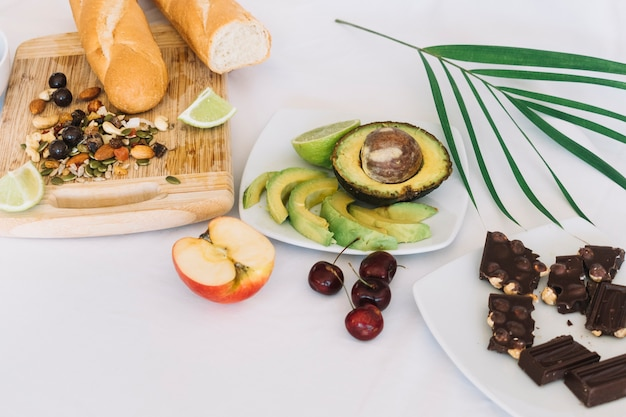 Chocolate; fruits and dryfruits with bread on white backdrop