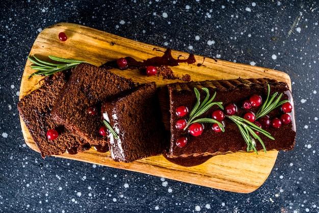 축제 배경에 초콜릿 진저 케이크입니다. 크리스마스 장식 테이블에 다크 초콜릿 토핑, 크랜베리, 로즈마리가 있는 전통적인 진저브레드 케이크, 복사 공간