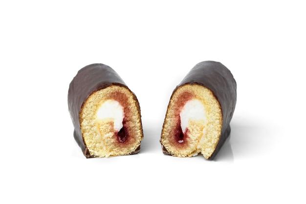 白い背景で隔離のベリージャムとチョコレートの艶をかけられたケーキロール。