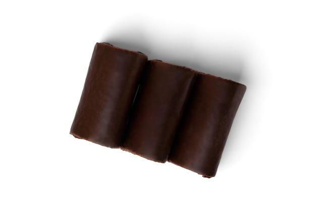 白い背景で隔離のベリージャムとチョコレートの艶をかけられたケーキロール。上面図。