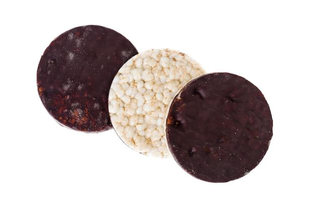 白い表面に分離されたチョコレート艶をかけられたデザート穀物クッキー