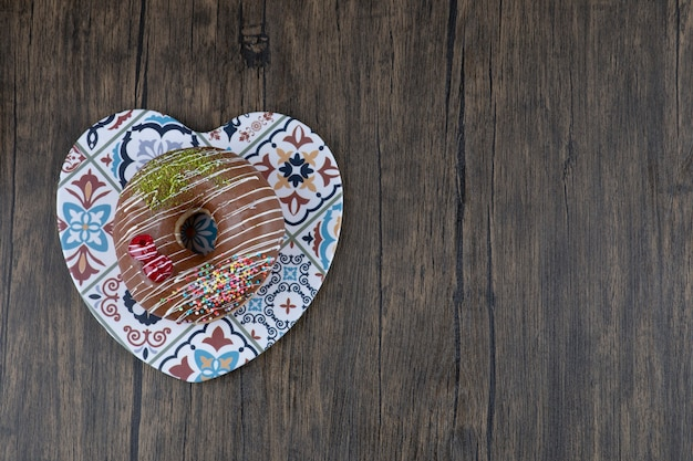 Chocolate glazed donut on colorful trivet on wooden surface.