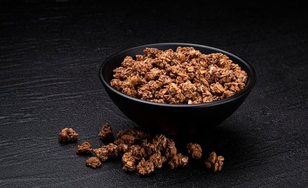 Chocolate granola on black bowl on black background