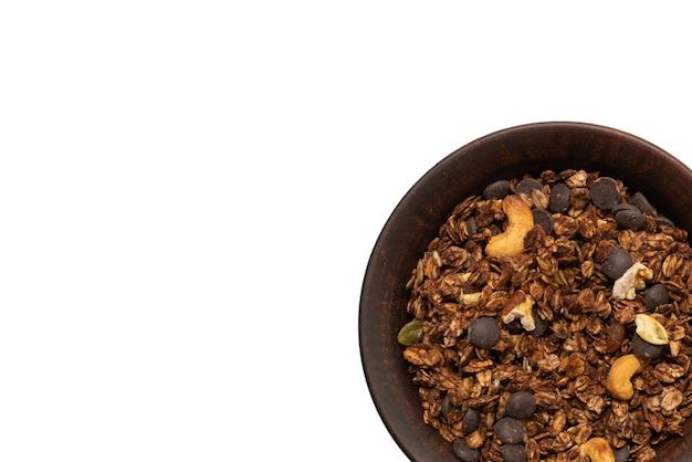 ボウルの表面にナッツが入ったチョコレートグラノーラシリアル。白いバックグラウンドで隔離されています。