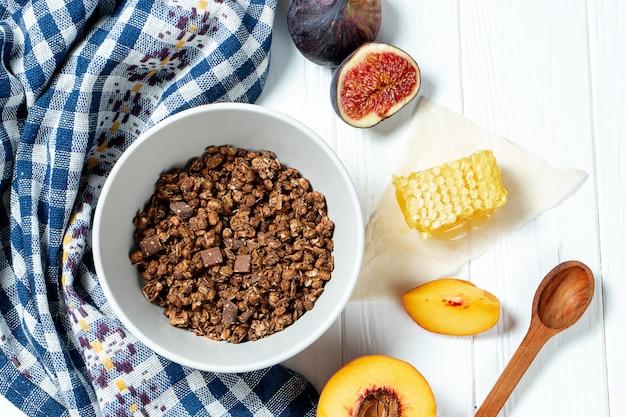 Шоколадная гранола в белой миске в составе с сотами, ложкой, инжиром и персиком.