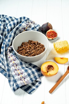 Chocolate granola in a white bowl in a composition with honeycombs, a spoon, figs and peach.