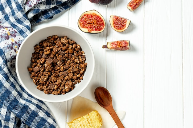 Chocolate granola in a white bowl in a composition with honeycombs, a spoon, figs on white wooden background.