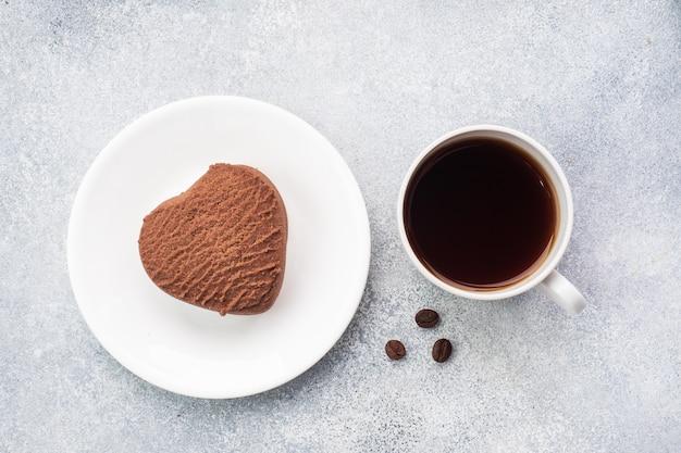 テーブルの上のチョコレートハートクッキーとブラックコーヒーのカップ、上面図。