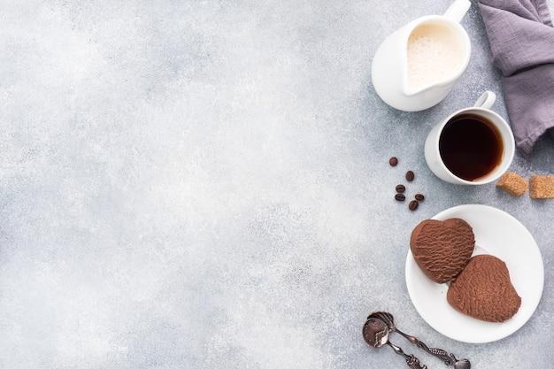 チョコレートハートクッキーとテーブルに牛乳とブラックコーヒーのカップ、上面図。スペースをコピーします。