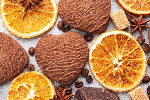 チョコレートハートクッキー、オレンジシナモン、灰色のテーブルのスパイシーなスパイス、上面図、クローズアップ。