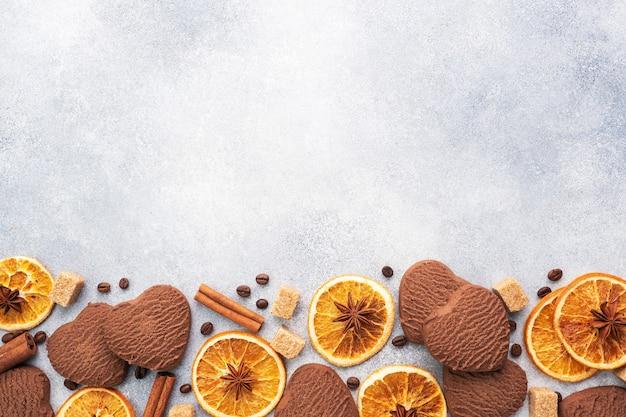 灰色のテーブル、上面図、コピースペースにチョコレートハートクッキー、オレンジシナモン、スパイシーなスパイス。