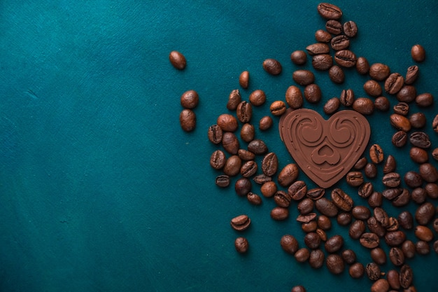 Шоколадное сердце лежит на темном фоне среди кофейных зерен