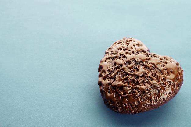 青い背景の上のチョコレートの心、クローズアップ