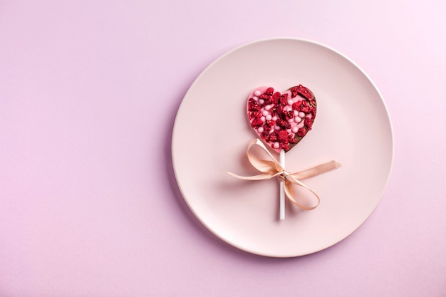 Chocolate heart on a pink plate on a pink background the concept of a romantic dinner valentines day
