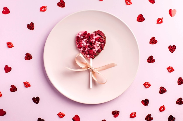 Chocolate heart on a pink plate on a pink background the concept of a romantic dinner
