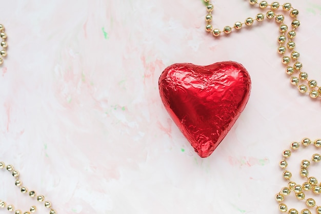 Chocolate heart in red foil on a pink background