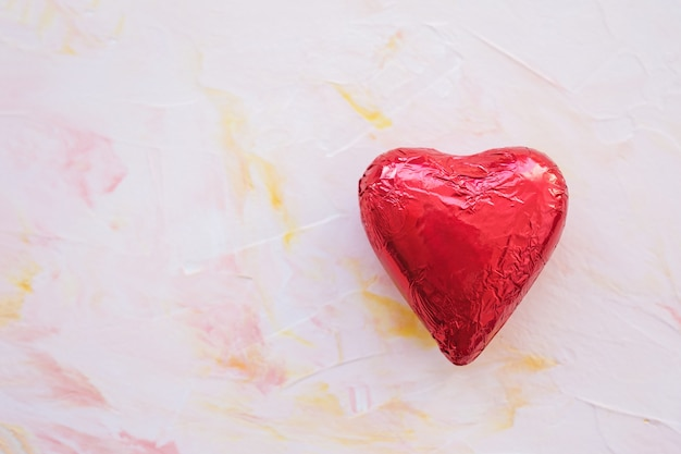 Chocolate heart in red foil on a pink