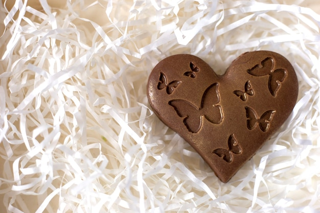 Chocolate heart with butterflies over white paper ribbons