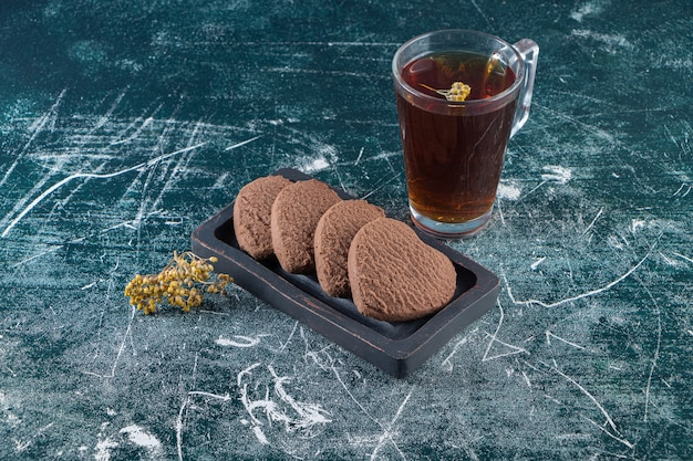 Chocolate hearts cookies with a cup of black tea placed on a stone table.