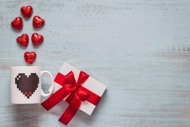 チョコレートのハート、マグカップ、明るい色の木製の背景に赤いリボンと白いプレゼント。上面画角、フラットレイ。バレンタインデーのコンセプト。コピースペース。